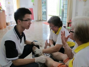 Jason Ling, a medical student, is now helping out with the Palliative Centre as a volunteer. Here he is learning from a cancer survivor Ah Lien.